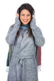 Cheerful beautiful model wearing winter clothes listening to music