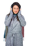 Peaceful model wearing winter clothes listening to music