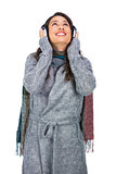 Smiling gorgeous model wearing winter clothes listening to music