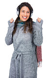 Smiling gorgeous model with winter clothes dancing while listening to music
