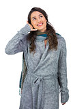 Smiling gorgeous model with winter clothes making phone call gesture