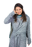 Cheerful model with winter clothes making phone call gesture
