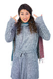 Curly haired model with winter clothes pointing out her head