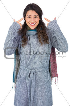 Smiling curly haired model with winter clothes pointing out her head
