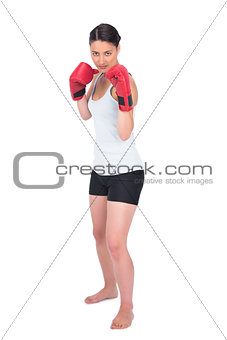 Serious young model in sportswear boxing