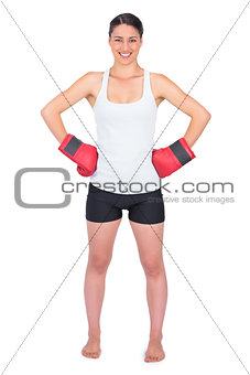Smiling young model with boxing gloves posing