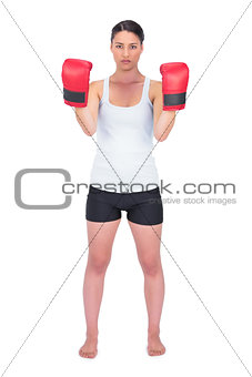 Angry healthy model with boxing gloves posing