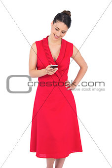 Smiling elegant brunette in red dress sending text message