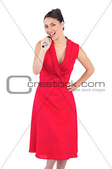 Happy elegant brunette in red dress singing
