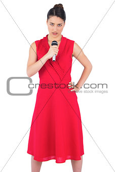 Serious elegant brunette in red dress singing