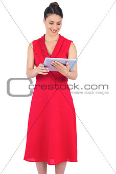 Content elegant brunette in red dress holding tablet pc