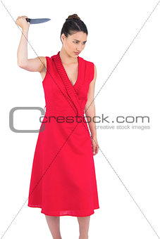 Angry elegant brunette in red dress holding knife