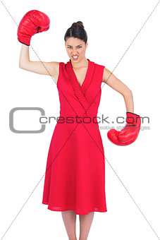 Angry gorgeous brunette in red dress wearing boxing gloves