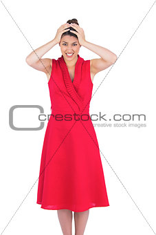 Anxious elegant brunette in red dress posing