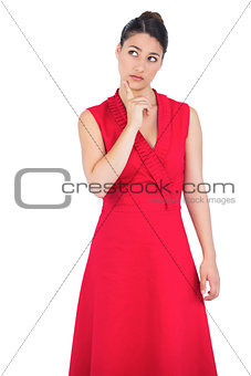 Thoughtful elegant brunette in red dress posing