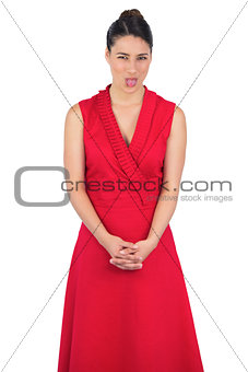 Elegant model in red dress sticking her tongue out