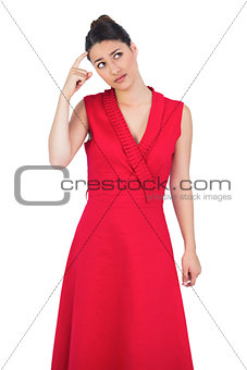Thoughtful glamorous model in red dress posing