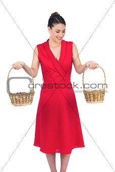 Content glamorous model in red dress holding baskets