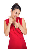 Cheerful sexy brunette in red dress thumbs up