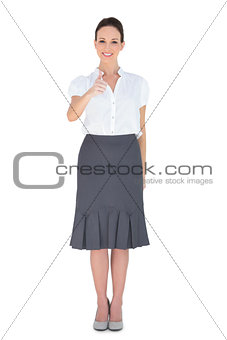 Cheerful businesswoman posing thumb up