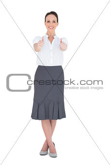 Smiling elegant businesswoman posing thumbs up