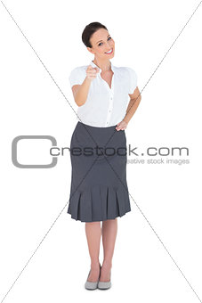 Smiling stylish businesswoman pointing at camera