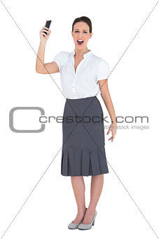Angry businesswoman shouting while holding her phone