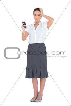 Worried businesswoman holding her phone