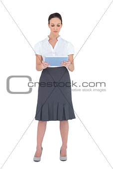 Focused pretty businesswoman using tablet computer