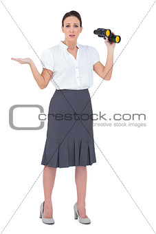 Worried elegant businesswoman holding binoculars