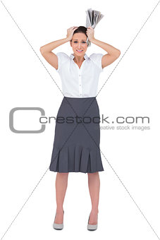 Worried stylish businesswoman holding newspaper