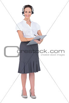 Attractive call center agent holding clipboard