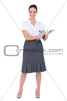 Beautiful businesswoman holding clipboard