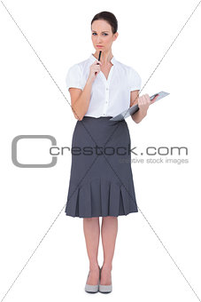 Thoughtful businesswoman holding clipboard