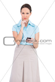 Thoughtful classy businesswoman holding smartphone