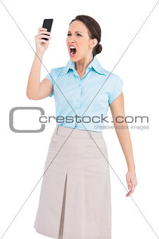Angry classy businesswoman shouting at her smartphone