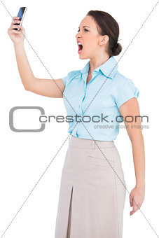 Angry classy businesswoman yelling at her smartphone
