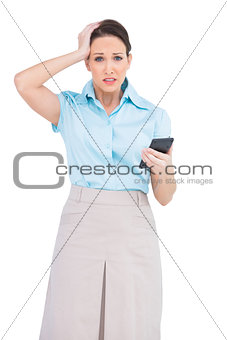 Worried classy businesswoman holding calculator