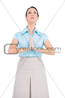 Upset young businesswoman praying