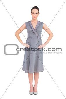 Serious elegant brunette in classy dress posing