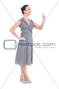 Happy elegant woman in classy dress pointing her finger