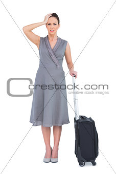 Worried gorgeous woman with suitcase posing
