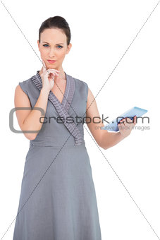 Thoughtful gorgeous woman holding digital tablet