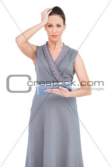Worried gorgeous woman holding digital tablet