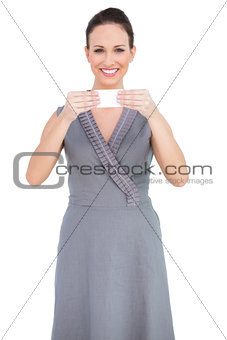 Cheerful seductive model holding business card