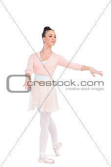 Calm attractive ballerina posing with her arms extended