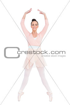 Smiling attractive ballerina standing on her tiptoes