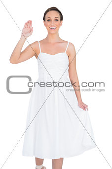 Smiling beautiful young model in white dress waving