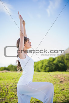 Peaceful young woman stretching outside