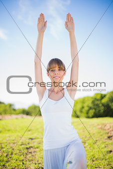 Happy young woman stretching outside
